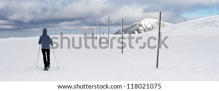 Person Walking on Snowy Path Leading to Sniezka - The Highest Peak of the Czech Republic, Krkonose Mountains - stock photo