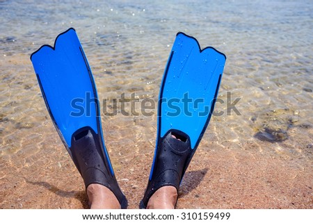 Person wearing a pair of blue rubber fins lying at the edge of the sea on the golden beach sand, view of the feet in a conceptual image of a summer vacation - stock photo