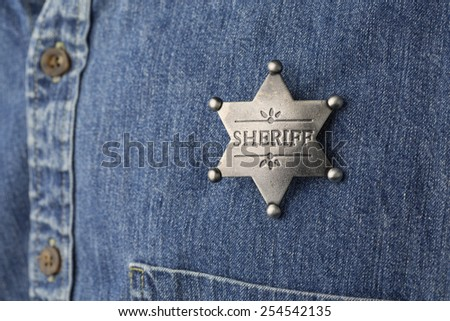 Person wearing faded denim shirt with a generic sheriff's badge.  - stock photo