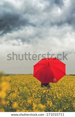 Person with Red Umbrella Standing in Oilseed Rapeseed Agricultural Field as Crop Protection Agrotech Concept, Selective Focus with Shallow Depth of Field - stock photo