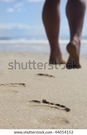 Person with strong calves walking on the beach - stock photo