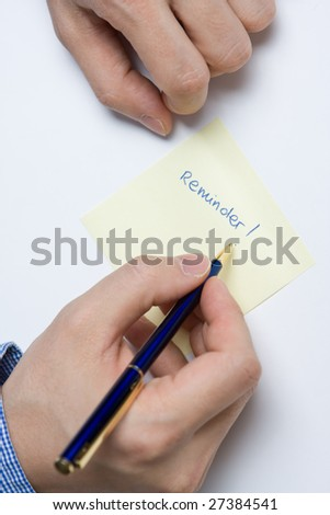 Person writing a message on a piece of paper or note - stock photo