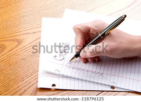 Person writing goals on a paper - stock photo