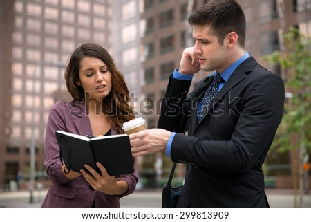Personal assistant with boss on the move fast pace high stress occupation downtown urban buildings - stock photo