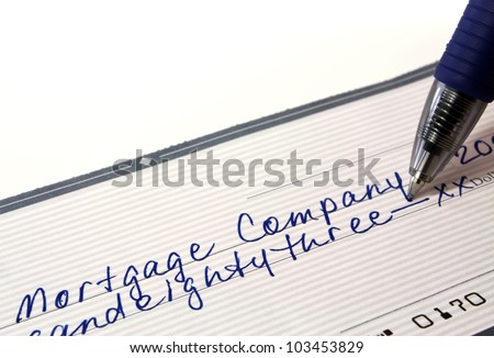 Personal bank check for mortgage payment with pen on white background with copy space. - stock photo