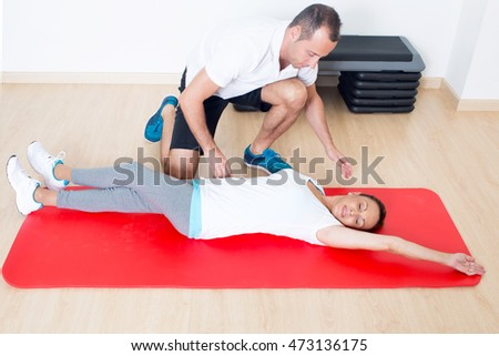 Personal coach correcting a stretching exercise of an elderly woman