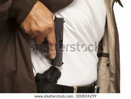 PERSONAL DEFENSE | Concealed Carry gun in holster on belt.  Mature adult with firearm or pistol. - stock photo