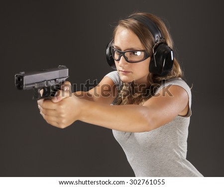 PERSONAL DEFENSE, GUN SAFETY | Young woman learning proper gun control and weapon safety, wearing proper safety glasses and ear protection.  Her finger is straight and off the trigger. - stock photo