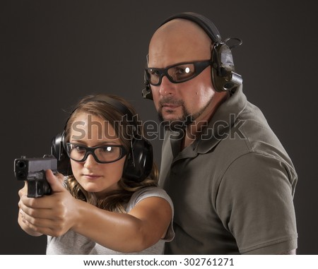 PERSONAL DEFENSE, GUN SAFETY | Young woman learning proper gun control and weapon safety with instructor, wearing safety glasses and ear protection.  Her finger is straight and off the trigger. - stock photo