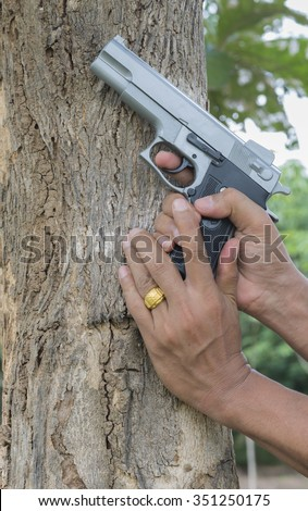 PERSONAL DEFENSE.Man pointing a gun at the target on nature background, selective focus. - stock photo