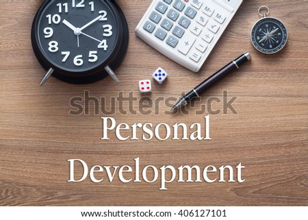 Personal Development written on wooden table with clock,dice,calculator pen and compass - stock photo