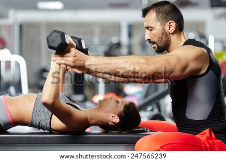 Personal fitness instructor helping a young woman with her chest workout - stock photo