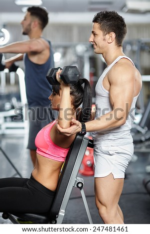 Personal fitness instructor helping a young woman work out with dumbbells - stock photo