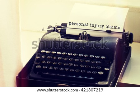Personal injury claims message on a white background against typewriter on a table - stock photo