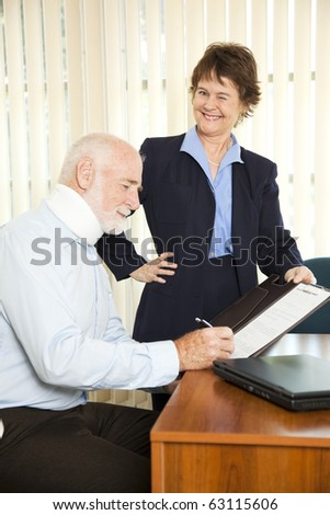 Personal injury lawyer winks as she signs a gullible client. - stock photo