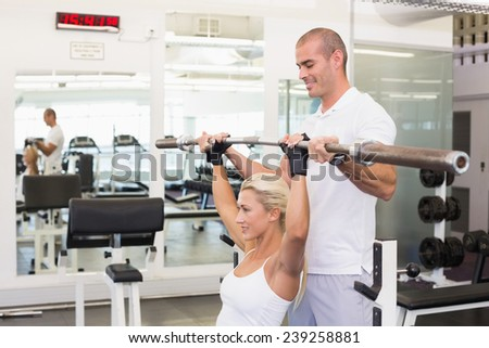 Personal male trainer helping young woman with lifting barbell in the gym - stock photo