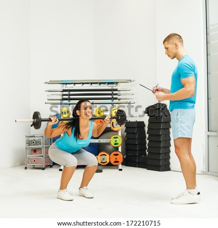 Personal male trainer watching young woman who to doing squats - stock photo