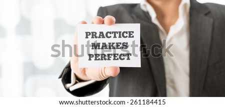 Personal mentor holding up a white card with a reminder Practice makes perfect. - stock photo
