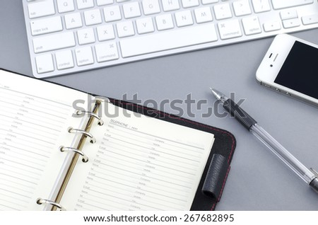 Personal organizer address book with pen and smart phone on Computer desk - stock photo
