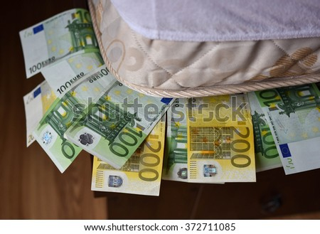 Personal savings deposited under the mattress - stock photo