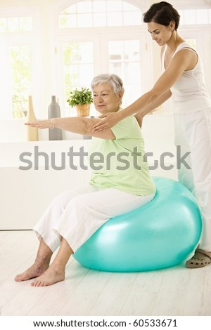 Personal trainer assisting senior woman doing fit ball exercise at home, smiling.? - stock photo