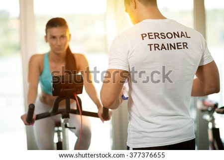 Personal trainer at the gym with client on bike  - stock photo