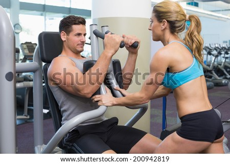 Personal trainer coaching bodybuilder using weight machine at the gym