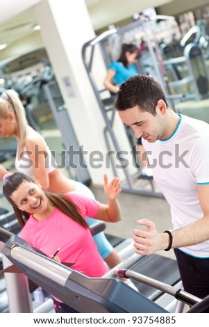 personal trainer encouraging man using treadmill at gym - stock photo
