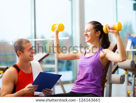 Personal trainer explaining an exercise to a woman - stock photo