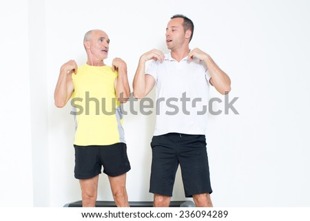 Personal trainer explains elderly man an exercise