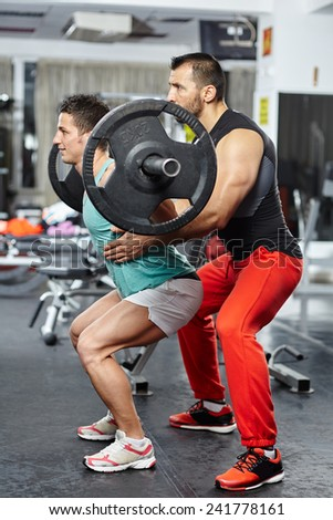 Personal trainer helping a young man doing squats with a heavy barbell - stock photo