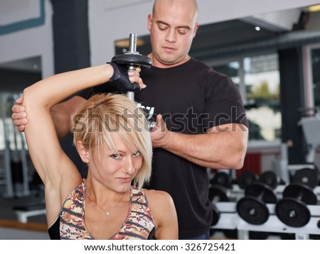 Personal trainer helping blonde woman in press of dumbbells. Sporty lifestyle, perfect body and abs, fitness, bodybuilding, training, healthy lifestyle and nutrition, diet and weight loss concept