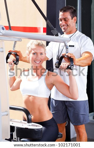 personal trainer helping client in gym - stock photo