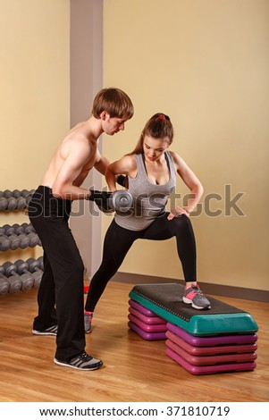 Personal trainer helping girl learn exercise with dumbbells. Fitness club. Weight loss program. Sport and health. - stock photo