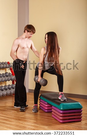 Personal trainer helping girl learn exercise with dumbbells. Fitness club. Weight loss program. Health and Sport. - stock photo