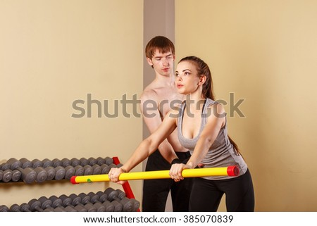 Personal trainer helping girl learn exercise with fitbar. Fitness club. Slimming program. Health and Fitness. - stock photo