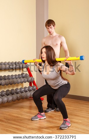 Personal trainer helping girl learn squat fitbar. Fitness club. Slimming program. Health and Fitness. - stock photo