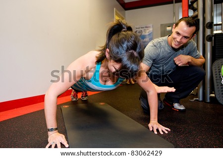 Personal Trainer helping woman do pushups. - stock photo