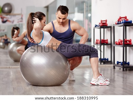 Personal trainer helping woman doing abs crunches with gym ball  - stock photo