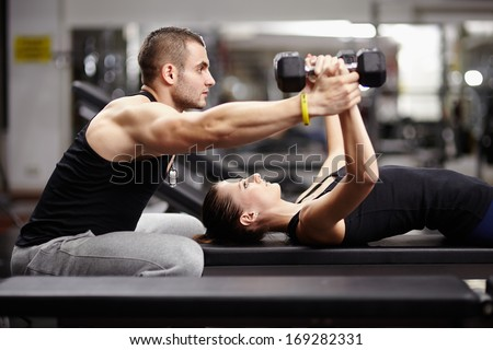 Personal trainer helping woman working with heavy dumbbells - stock photo