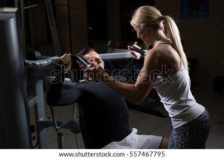 Personal trainer helping woman working with heavy dumbbells.