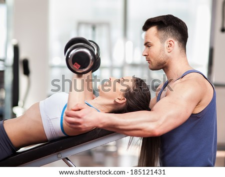 Personal trainer helping woman working with heavy dumbbells at the gym - stock photo