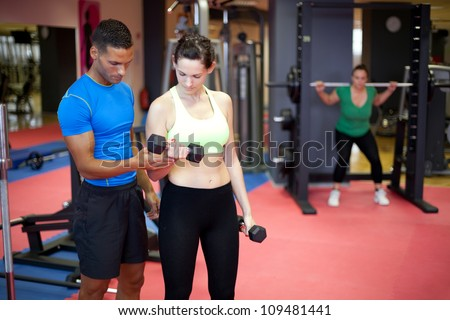 Personal trainer helping young woman bicep exercise in the gym. Selective focus. - stock photo