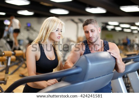 Personal trainer helps set the treadmill in gym - stock photo