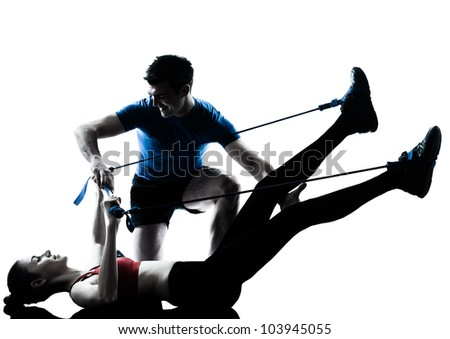 personal trainer man coach and woman exercising gymstick silhouette  studio isolated on white background - stock photo