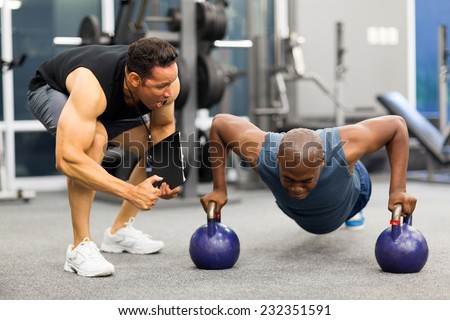personal trainer motivates client doing push-ups in gym - stock photo
