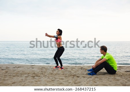 Personal trainer observing how young woman doing squat exercises, fitness couple training on the beach against sea at evening time  - stock photo