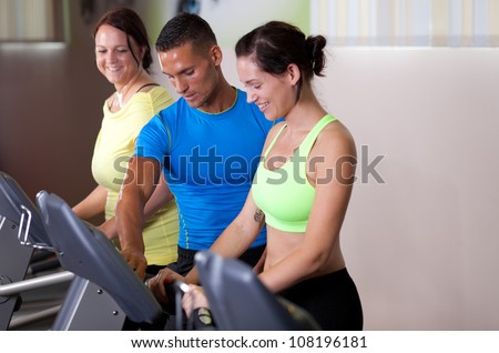 Personal trainer setting treadmill for a couple of young women - stock photo