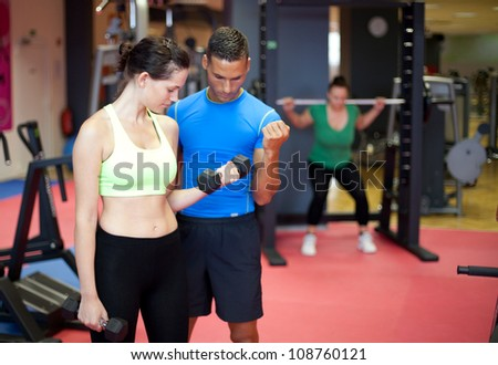 Personal trainer showing a young woman a bicep exercise - stock photo