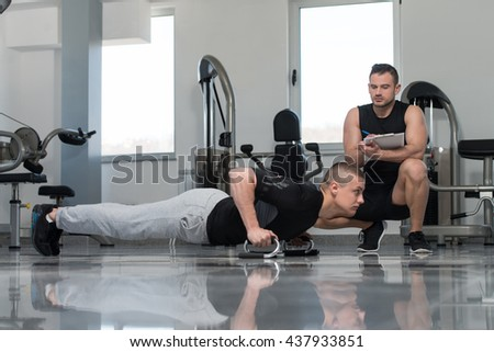 Personal Trainer Showing Young Man How To Exercise Push-Up Strength In A Health And Fitness Concept - stock photo